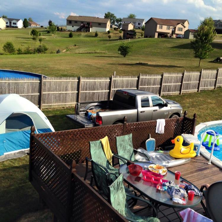 Backyard camping with a pool and a tent.