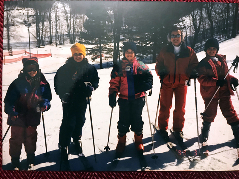 Four girls stand on skis with a mom. Faded picture of a printed photo.